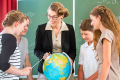 O professor educa os estudantes que têm lições da geografia na escola Imagens de Stock