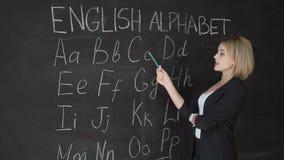 O professor está escrevendo a letra do alfabeto no quadro-negro com giz Educação no conceito da escola primária filme