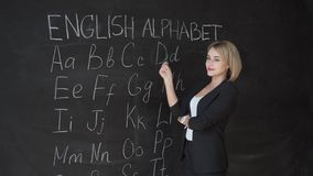 O professor está escrevendo a letra do alfabeto no quadro-negro com giz Educação no conceito da escola primária vídeos de arquivo