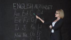 O professor está escrevendo a letra do alfabeto no quadro-negro com giz Educação no conceito da escola primária video estoque