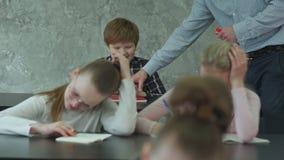 O professor está irritado porque menino de escola que joga jogos no smartphone durante a classe video estoque