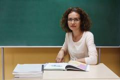 O professor está sentando-se na mesa da escola perto do quadro-negro Foto de Stock Royalty Free