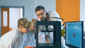 O professor explica o processo de impressão das crianças 3D em um laboratório vídeos de arquivo