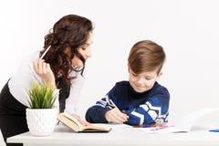 O professor fêmea ajuda o menino adolescente a fazer seus trabalhos de casa Fazendo trabalhos de casa junto foto de stock