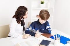 O professor fêmea ajuda o menino adolescente a fazer seus trabalhos de casa Fazendo tarefas junto fotos de stock royalty free