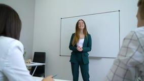 O professor fêmea positivo de sorriso e os estudantes alegres dizem gracejos na atmosfera amigável na sala de aula filme