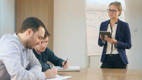 O professor fêmea seguro de sorriso com um tabuleta-PC realizou em suas mãos que estão na frente da classe Fotografia de Stock Royalty Free