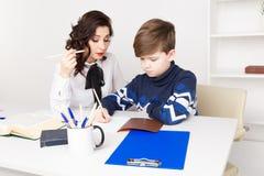 O professor f?mea ajuda o menino adolescente a fazer seus trabalhos de casa Fazendo trabalhos de casa junto fotos de stock royalty free