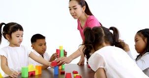 O professor joga blocos de madeira coloridos com estudante vídeos de arquivo