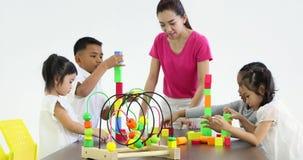 O professor joga blocos de madeira coloridos com estudante filme