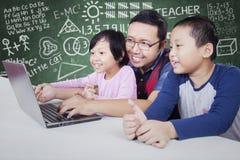 O professor masculino ensina dois estudantes com portátil Imagem de Stock