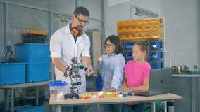 O professor mostra a crianças o robô na classe da ciência da tecnologia