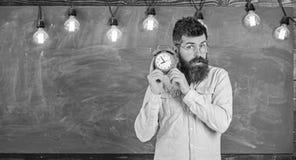 O professor nos monóculos guarda o despertador Homem com barba e bigode no pulso de disparo de escuta concentrado da cara bearded fotos de stock