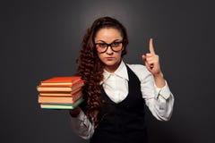 O professor novo nos vidros com a pilha dos livros faz o sinal da atenção Fotografia de Stock
