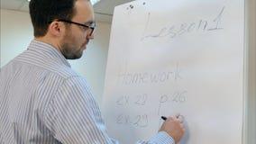 O professor novo nos vidros que escreve em casa o trabalho exercita no flipchart Imagens de Stock
