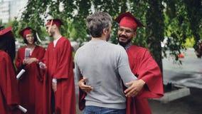 O professor orgulhoso está felicitando o estudante, está agitando sua mão e está abraçando-o no dia de graduação que está no terr vídeos de arquivo