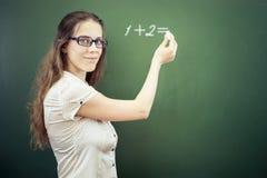 O professor ou o estudante escreveram no quadro-negro com giz na sala de aula foto de stock
