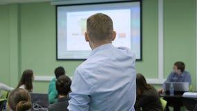 O professor profissional na sala de classe na universidade está entregando a leitura na economia que aponta destaques e esquemas video estoque