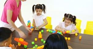 O professor que joga blocos coloridos brinca com estudante video estoque