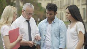 O professor superior que mostra o app educacional novo na tabuleta aos estudantes, MBI estuda filme