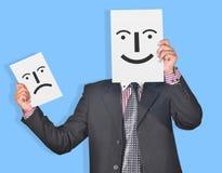 O profissional com a cara feliz & triste sorri nas mãos Imagens de Stock Royalty Free