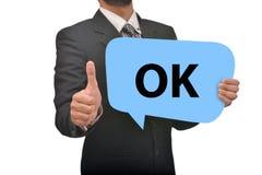 O profissional que mantém a bolha aprovada do discurso disponivel com polegares levanta a impressão Imagens de Stock Royalty Free