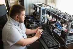 O programador configura o hardware para a mineração do bitcoin foto de stock