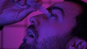 O programador Hacker Pouring Medicine do Gamer deixa cair em seus olhos foto de stock