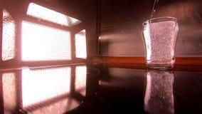 O projetor ilumina acima o derramamento dentro de um vidro da água no movimento lento filme