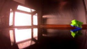 O projetor ilumina acima a queda de uma esponja molhada no movimento lento filme