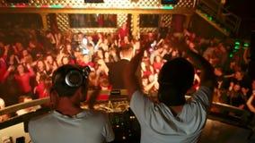 O projetor ilumina uma multidão de povos que dançam em um concerto com DJs profissional vídeos de arquivo