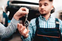 O proprietário de carro dá chaves ao mecânico In Garage fotos de stock royalty free