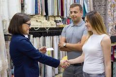 O proprietário de loja fêmea dá o cartão aos pares novos Loja de matéria têxtil da casa da empresa de pequeno porte imagens de stock