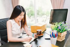 O proprietário empresarial pequeno asiático trabalha em casa o escritório, usando a chamada de telefone celular, escrevendo confi fotografia de stock