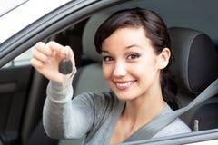 O proprietário feliz de um carro novo está mostrando a chave do carro foto de stock royalty free