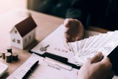O proprietário novo entregou os conceitos de troca do dinheiro e dos bens imobiliários fotos de stock royalty free