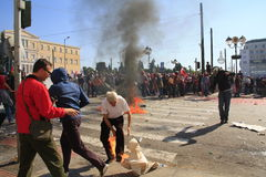 O protestador tenta põr para fora o incêndio sobre seus pés Imagens de Stock