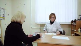 O psicólogo da mulher dá um cartão para um teste a um paciente Louro em uma recepção com um psicólogo filme