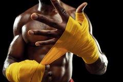 O pugilista afro-americano está envolvendo as mãos com atadura foto de stock