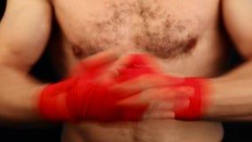 O pugilista ascendente próximo do homem aperta os pulsos com envoltório vermelho filme