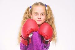 O pugilista da menina sabe se defenda Crian?a da menina forte com as luvas de encaixotamento que levantam no fundo branco Apronta fotografia de stock