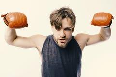 O pugilista demonstra seus músculos fortes O homem com cerda e a cara impudente veste luvas de encaixotamento Atleta com caixa de fotografia de stock