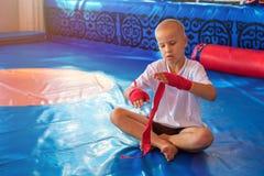 O pugilista do menino no gym envolve suas mãos com ataduras fotos de stock royalty free