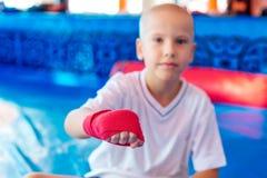 O pugilista do menino no gym envolve suas mãos com ataduras fotografia de stock royalty free
