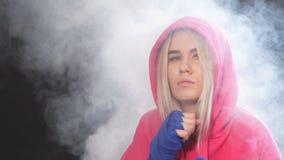 O pugilista fêmea prepara-se para perfurar no estúdio do encaixotamento Pugilista da mulher no movimento sobre o fundo fumarento  video estoque