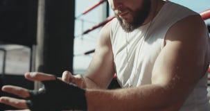 O pugilista masculino envolve suas mãos com handwrap preto antes do treinamento da luta filme