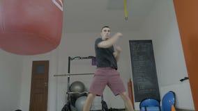 O pugilista masculino novo atlético que veste fazer ocasional da roupa do gym aquece exercícios de braço antes de começar encaixo vídeos de arquivo