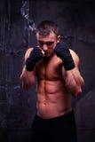 O pugilista muscular forte está pronto para lutar o levantamento sobre o backgr preto Imagem de Stock