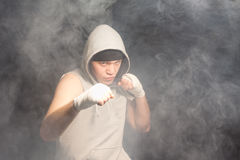 O pugilista novo que luta em um fumo encheu a atmosfera fotografia de stock