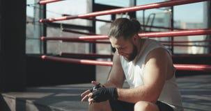 O pugilista põe disponível envoltórios ao se sentar na borda de um anel de encaixotamento em um gym de encaixotamento, a câmera g vídeos de arquivo